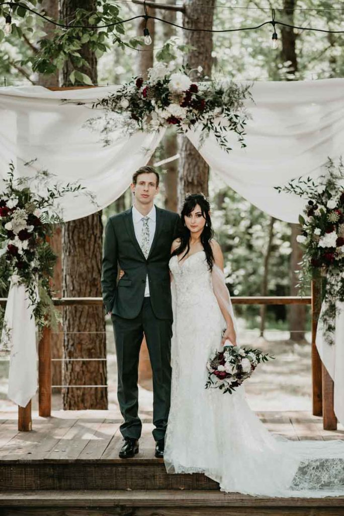 two people under white draped arbor and florals from Fox and Fern florist from Chattanooga TN